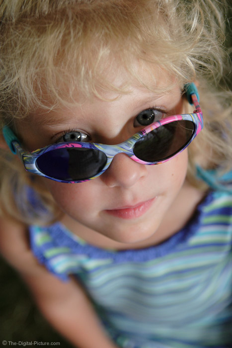 Girl Peering Over Sunglasses Picture