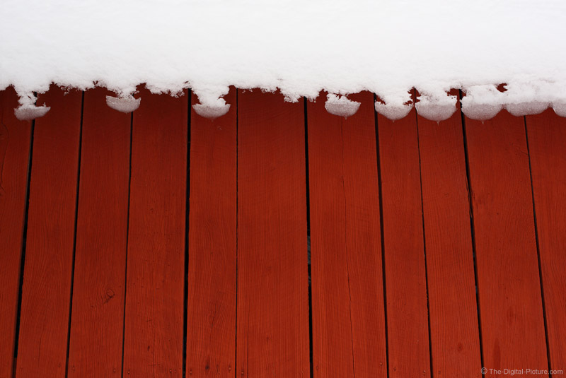 Snow Falling from Red Barn